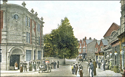 Postcard of an early car in High Street, Rushden